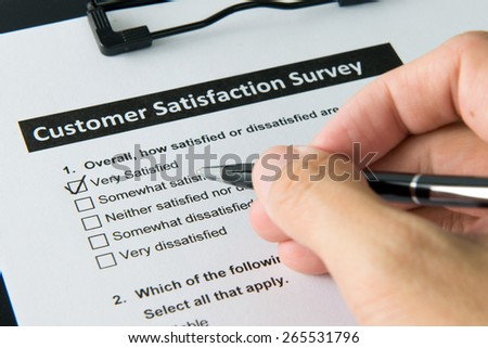 Filling customer satisfactory survey form with pen - stock photo