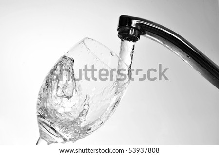 Filling  glass with fresh water from  faucet - stock photo