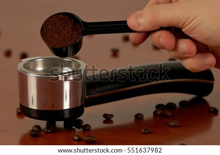 filling in the coffee machine's spoon with coffee