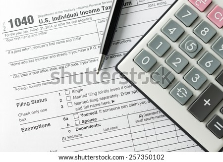 Filling income tax form with pen and calculator