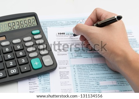 Filling out income tax forms with calculator and pen - stock photo