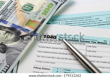 Filling out income tax forms with US dollar and pen - stock photo