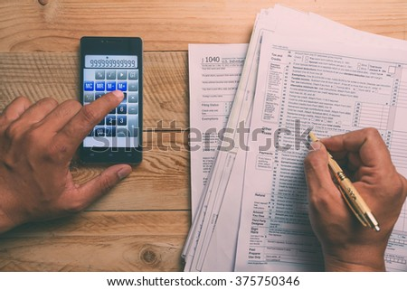 Filling 1040 tax form, surrounded with other document and a calculator - stock photo