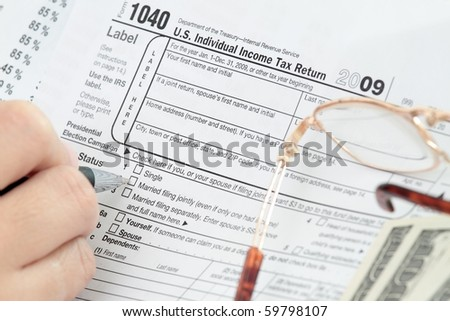 Filling the 1040 Tax Form with dollars and eyeglass - stock photo