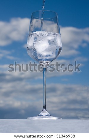 filling water in glass with ice on cloudy sky background - stock photo