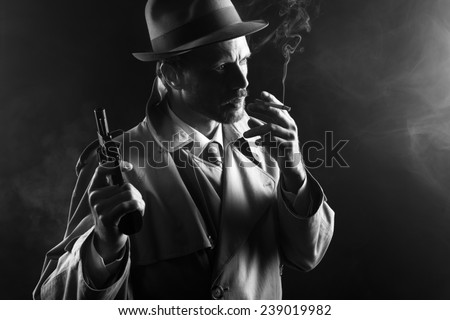 Film noir: attractive gangster in trench coat smoking a cigarette and holding a revolver - stock photo