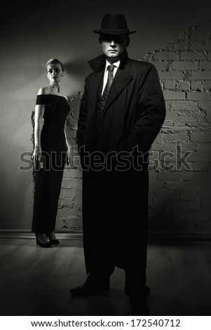 Film noir. Detective man in a raincoat and hat and a dangerous woman with a gun in his hand - stock photo