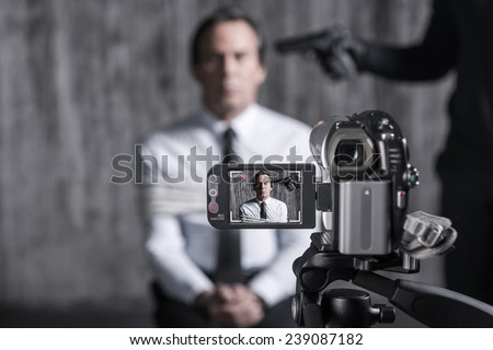 Filming hostage. Tied up businessman caught by a criminal sitting in front of a dirty wall with gun near his head while video camera filming it on the foreground - stock photo