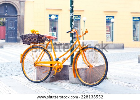 Filtered image of orange provence rural retro bicycle with fruits in wicker basket. Sunshine summertime outdoors. - stock photo