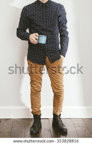 filtered photo of a young stylish man holding a coffee - stock photo
