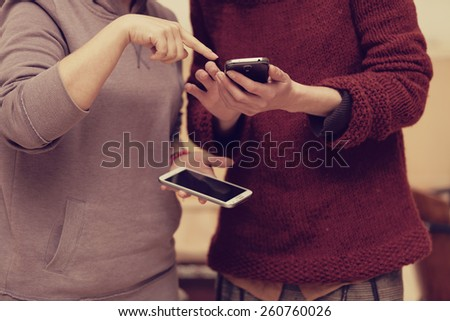 filtered photo of two friends using their smart phones outdoors - stock photo
