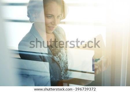 Filtered portrait of an executive business woman writing on a glass wall at sunset - stock photo