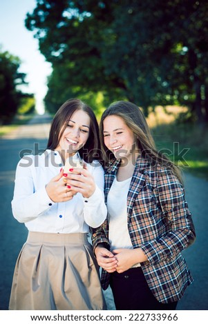 Filtered portrait of 2 happy pretty sisters in formal wear looking on mobile phone and laughing on green outdoors copy space background - stock photo