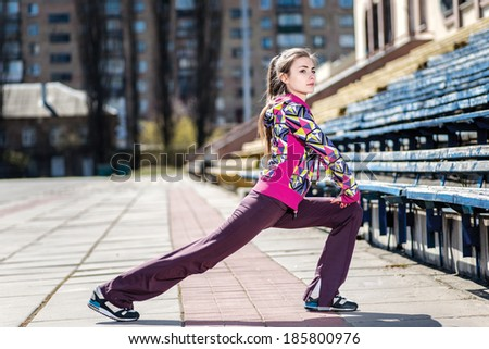 Final stretch! Young and attractive woman stretches outdoors at the stadium - stock photo