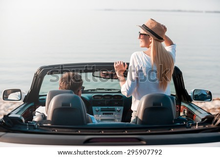 Finally arrived! Rear view of smiling young woman enjoying scenery while her boyfriend sitting near on front seat of their convertible  - stock photo