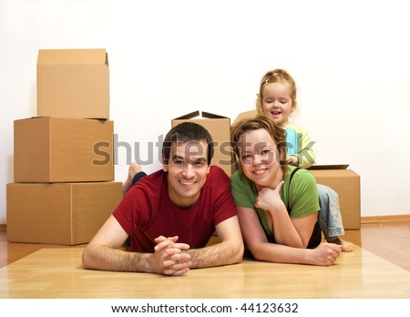 Finally in our new home - young family laying on the floor among cardboard boxes, moving concept