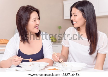 Finally together. Asian Mommy and daughter discussing day at table - stock photo