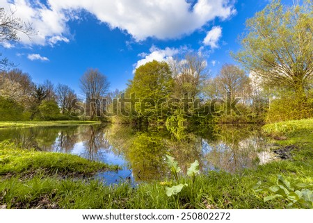 Finaly it is Spring in this natural park with pond and ecological banks in april. Young leaves are emerging on branches. - stock photo