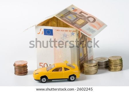 Finance A house made of money (Euro). A car before it and some coins. Building a house is expensive! - stock photo