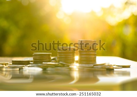 Finance and Money concept, Money coin stack growing graph with sunlight and water reflection - stock photo