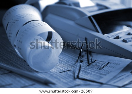 Finance concept: Day Trading Blues. Adding machine on top of stock market stats. glases and pencil left behind. Titnted blue to add to metaphor. - stock photo