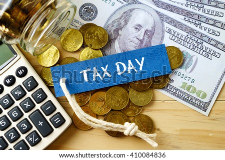 Finance conceptual image with TAX DAY words, hundred dollar bills, golden coins and calculator on wooden background.
