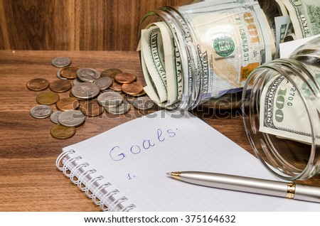 finance idea - new years resolutions with dollar in glass jar, coins on wooden table