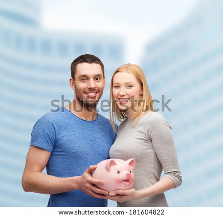 finance, money and family concept - smiling couple holding big piggy bank - stock photo