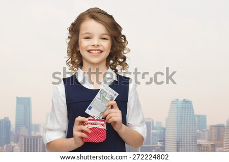 finances, childhood, people and savings concept - happy little girl with purse and paper euro money over city background - stock photo