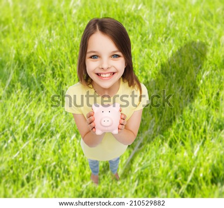 finances, childhood, saving and people concept - beautiful little girl with piggy bank - stock photo