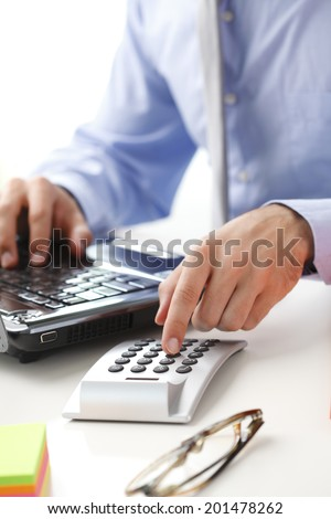 Financial adviser calculating data while working at bank.