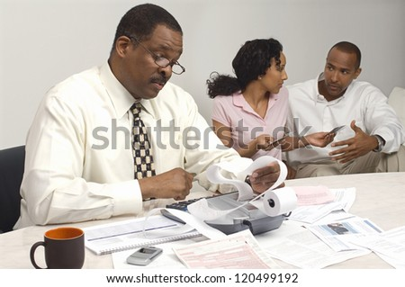 Financial adviser holding expense report with couple having discussion in the background