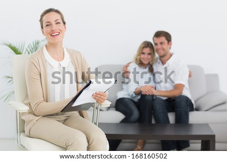 Financial adviser writing notes with young couple in background at home