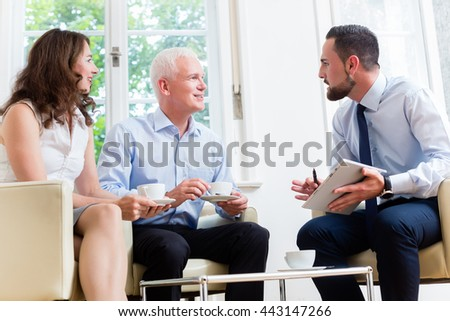 Financial advisor consulting couple in retirement planning in modern, luminous office - stock photo