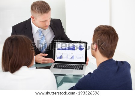 Financial advisor explaining investment plan to couple on laptop at office desk - stock photo