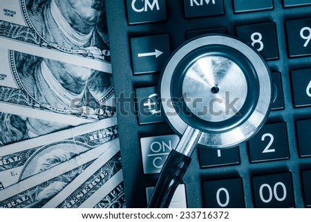 Financial analysis, audit or accounting - Stethoscope over a calculator and dollar bills toned in blue - stock photo