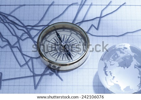 financial analysis/Close-up of a compass on stock market data chart  with crystal globe - stock photo