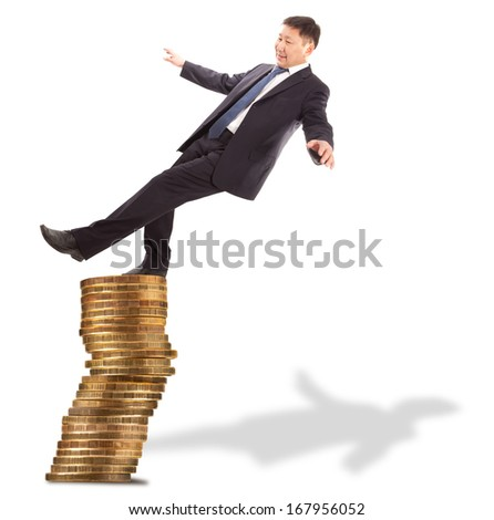 Financial and crisis concept. Asian businessman standing on the unstable coins  - stock photo