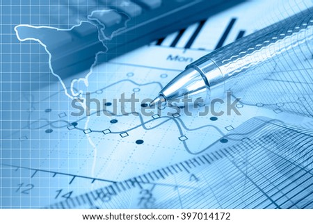 Financial background in blues with map, calculator, graph and pen. - stock photo