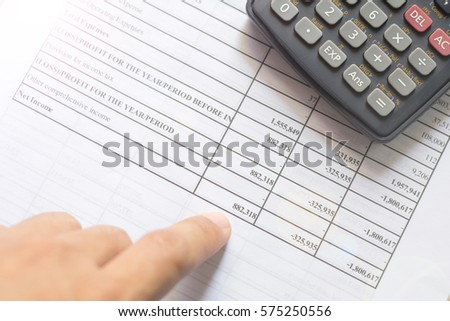 Financial budget statement and calculator on the table. Businessman reading Financial budget statement of stock market investment.