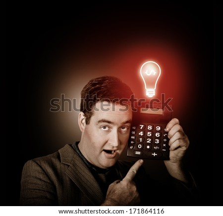 Financial business man with shocked expression pointing to calculator with switched on red light bulb. Money idea - stock photo
