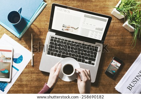 Financial business news online on a laptop with coffee and stationery - stock photo
