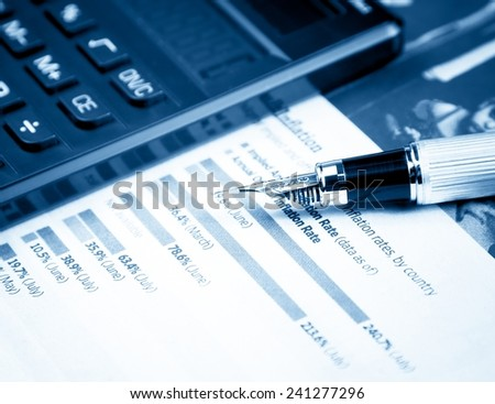 financial chart and graph near pen and calculator on the table