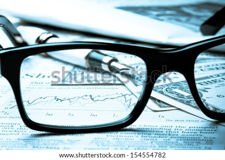 financial chart near dollars seen by unfocused glasses - stock photo