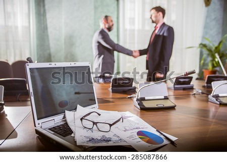 financial chart near dollars seen by unfocused glasses ( colleagues meeting to discuss their future financial plans only silhouettes being viewed )  two businessmen shake hands - stock photo
