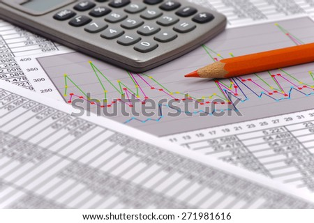 financial chart on table of data with calculator - stock photo