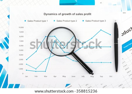 Financial chart with a magnifying glass. Report on sales for current year - stock photo
