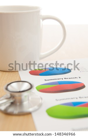 Financial charts and graphs with Stethoscope - stock photo