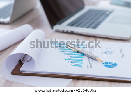Financial charts on the table with laptop - stock photo
