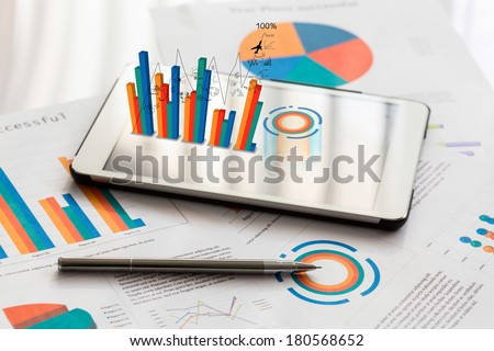 Financial charts on the table with tablet phone and pen - stock photo